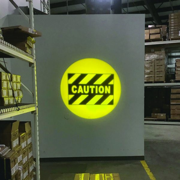 Yellow caution logo displayed from an LED projector on a warehouse wall