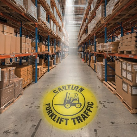 Yellow caution forklift traffic logo from an LED safety projector displayed on the floor of a warehouse