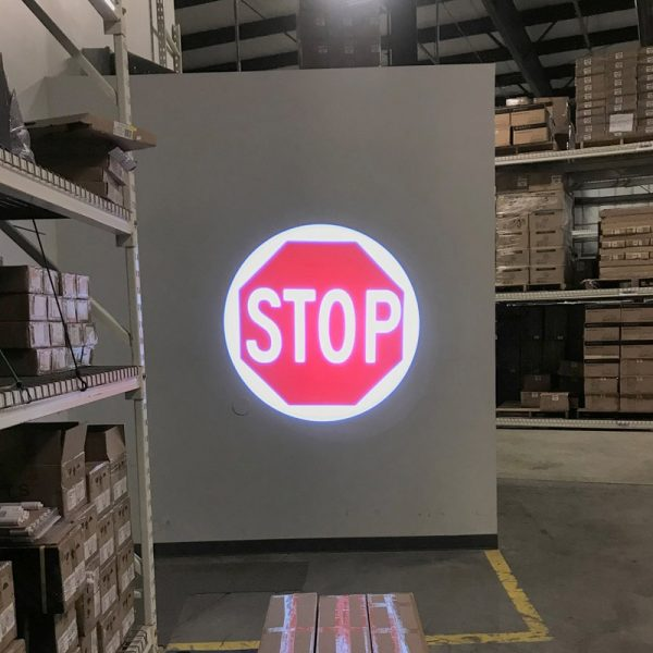 Red stop sign logo displayed from an LED projector on a warehouse wall
