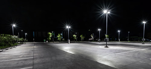 An empty parking lot with lights brightly illuminating the area