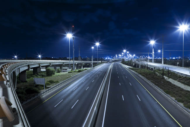 A highway at night being illuminated by bright LED street lights