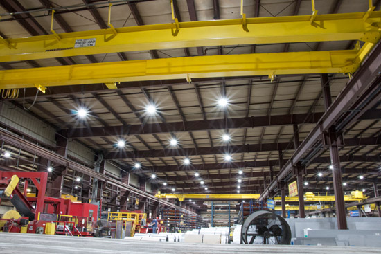 Round shaped LED UFO High Bay Lights illuminating a large warehouse space filled with construction equipment
