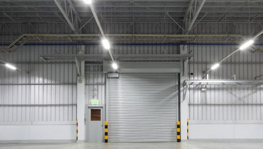 LED T8 tube strip lights illuminate a large commercial warehouse with a loading dock gate centered in the middle.